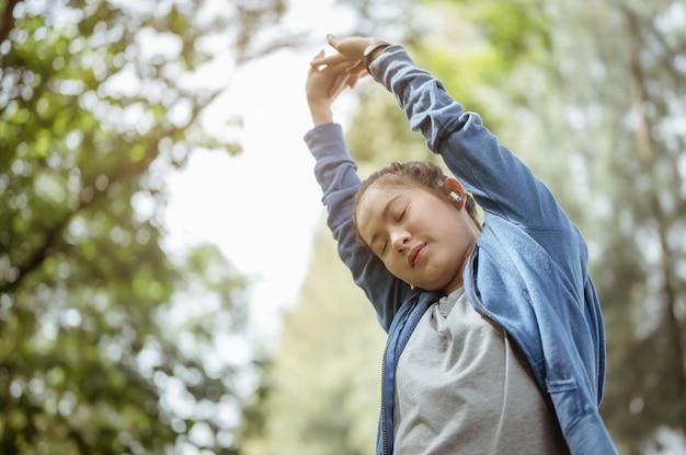 アジアの女の子は週末の運動で運動し、自然公園で彼女の体を伸ばしています