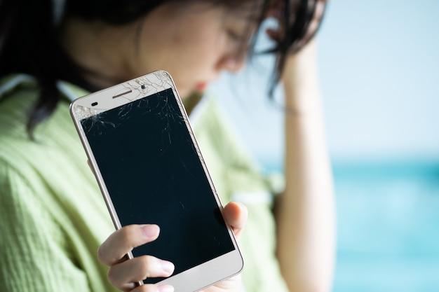 彼女の電話が壊れているので、アジアの女の子は悲しんでいます