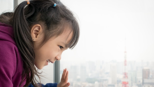 Asian girl is looking out to tokyo city from windows