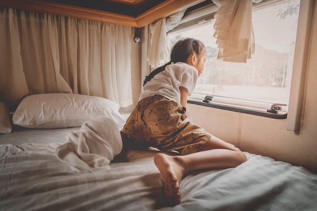 Asian girl is looking out the window in a trailer home. Premium Photo