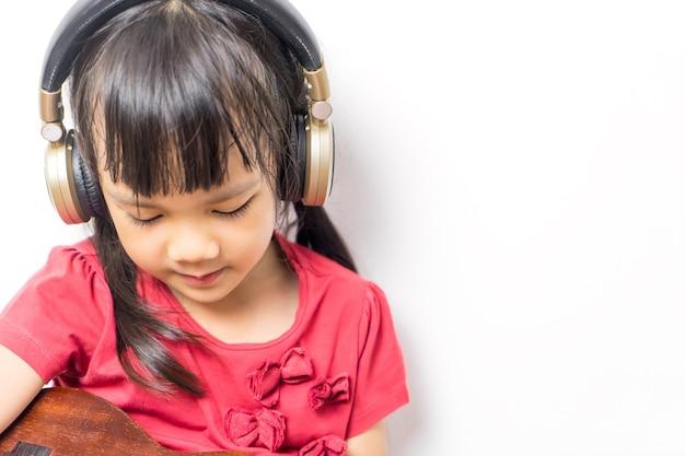 アジアの女の子は、白い背景にヘッドフォンで音楽ギターを再生しています。