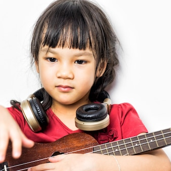 Asian girl is playing music guitar with headphone on white background