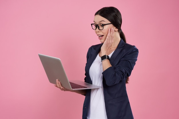 Asian girl is posing with laptop on pink background.