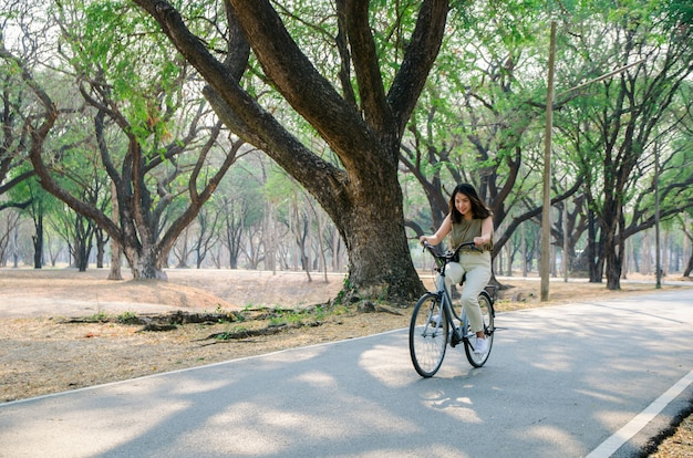 Asian girl is riding bicycle on road in park with smile face
