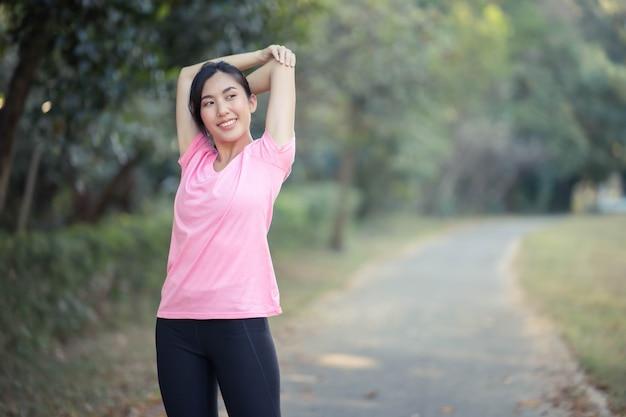 아시아 소녀는 공원에서 달리기 전에 몸의 따뜻한 근육을 스트레칭합니다.