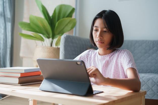 アジアの女の子はタブレットでインターネットを介してオンラインで勉強しています