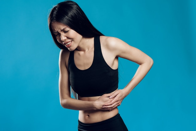 Asian girl is suffering from the back sprain.