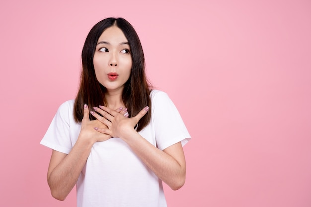 Asian girl is surprised she is excited. pink background studio.