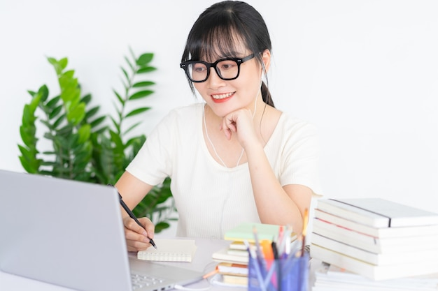Asian girl is taking notes and studying online via laptop