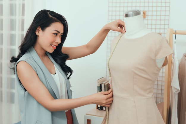 An asian girl  is working in the workshop studio. she makes fitting on the dress on the mannequin.