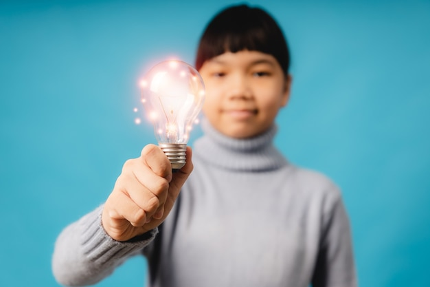 Asian girl kid holding lighting bulb of creative idea and bright learning imagine, learn and education concept