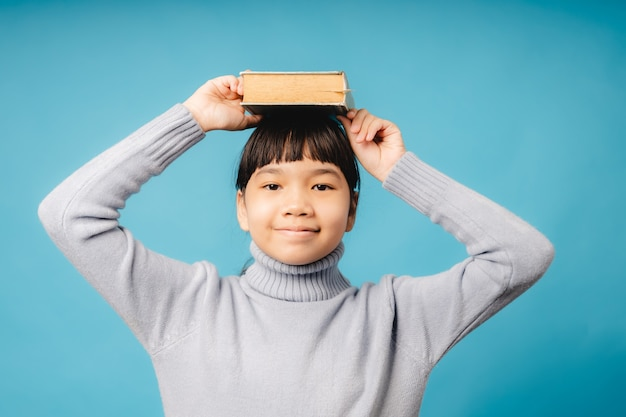 Asian girl kid holding text book on head of creative idea and bright learning imagine, learn and education concept