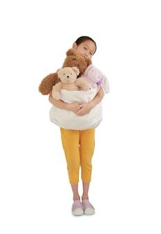 아시아 여자 아이가 기부를 위해 장난감 가방을 껴안고 있습니다. 클리핑 패스와 함께 흰색 배경에 고립 된 인형의 아이 포옹 가방. 다른 사람에게 행복을 전달하고 공유하는 개념