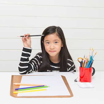 Asian girl kid thinking about what to draw and holding pencil in hand on white table