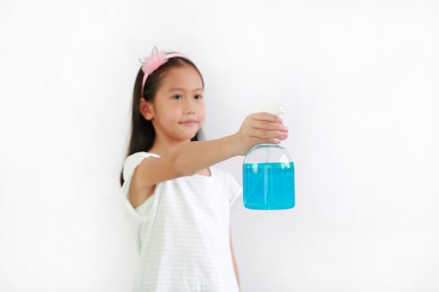 흰색 바탕에 코로나바이러스 전염병 발병에 대항하기 위해 병 스프레이 알코올 액체를 사용하는 아시아 여자 아이, 방부제. 아이 손과 알코올 병에 선택적 초점