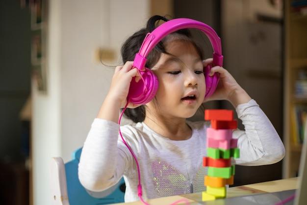 헤드폰과 노트북으로 배우는 아시아 소녀, 행복한 소녀는 집에서 노트북으로 온라인으로 배웁니다.