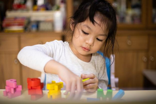 自宅でアルファベットを学ぶアジアの女の子。新しい通常。 covid-19コロナウイルス。人混みを避ける。家にいる