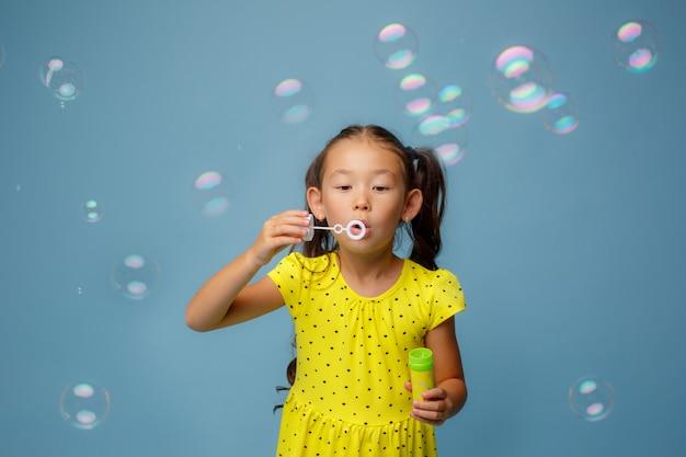Азиатская девушка letn мыльные пузыри в студии на синем
