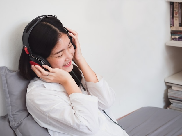Asian girl listening music in headphones on bed