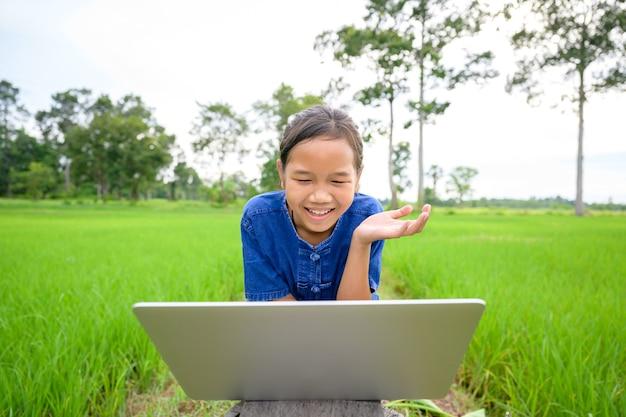 태국 시골 지역에 사는 아시아 소녀와 태국 시골 지역 학교 초등학생들이 집에서 노트북으로 교재를 보고 논에서 온라인으로 공부하고 있다.