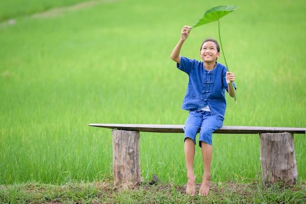 시골에 사는 아시아 소녀 그녀는 태국 시골의 논에 행복하게 앉아 있습니다. 자연 한가운데 있는 논에서 웃고 행복한 아시아 소녀.