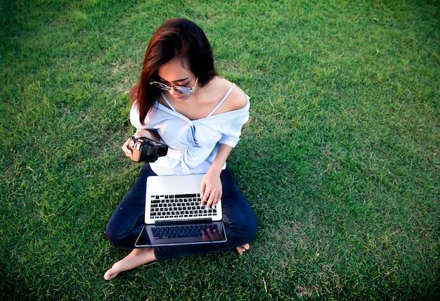 Азиатская девушка смотрит цифровую камеру