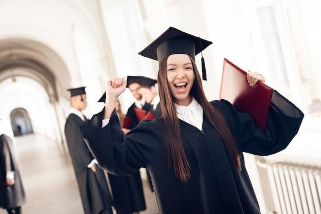 Asian girl in mantle is standing in corridor of university