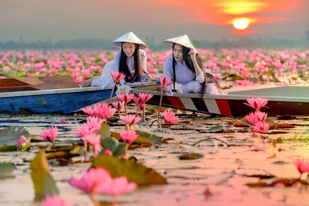 Asian girl in national costume of vietnam sitting on the boat in red lotus sea in undon thani, thailand.