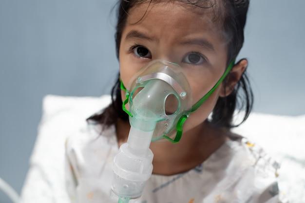 아시아 소녀는 그녀의 얼굴에 흡입기 마스크를 통해 분무를 필요로