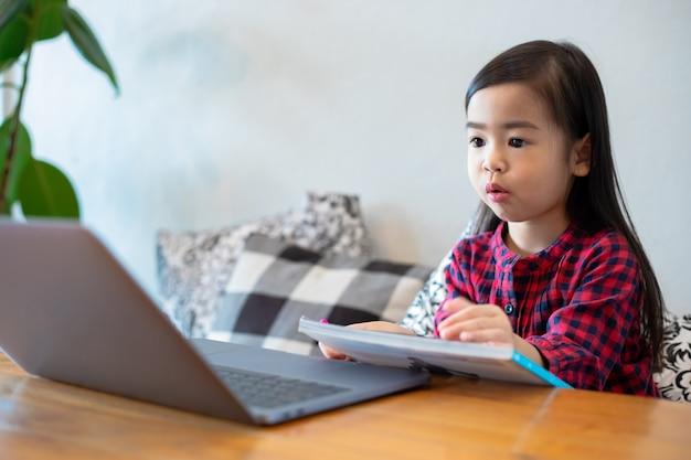 Азиатские девушки или дочери используют тетради и технологии для онлайн-обучения во время школьных каникул и просмотра мультфильмов дома. образовательные концепции и деятельность семьи