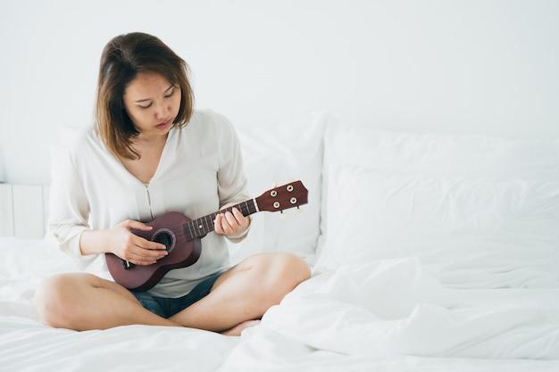 아시아 소녀 아침 일어나서 기타를 연주합니다. 밝게 느끼기