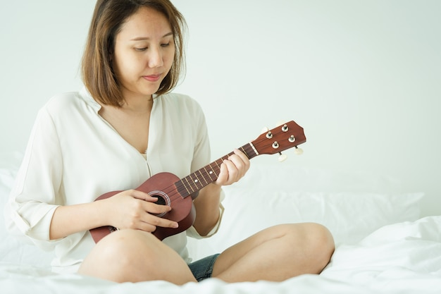 Asian girl play the ukelele