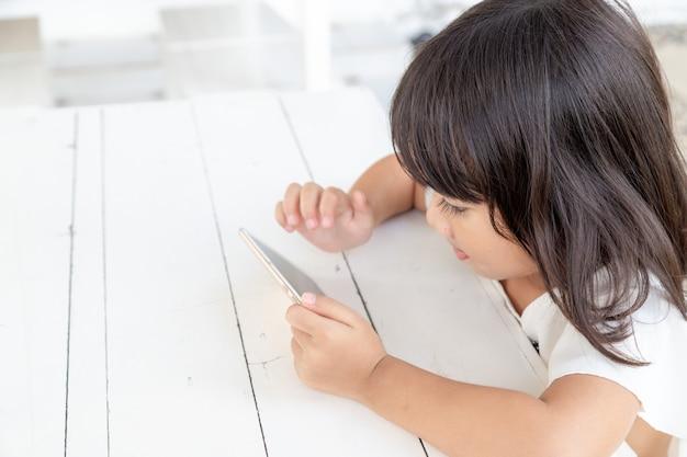 スマートフォンを見てテーブルの上でスマートフォンを遊んでいるアジアの女の子子供たちは電話を使用してゲームをします