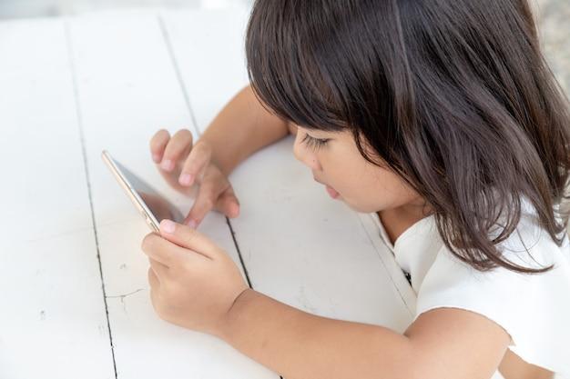 스마트폰을 보고 테이블에서 스마트폰을 하는 아시아 소녀 아이들은 전화를 사용하고 게임을 합니다