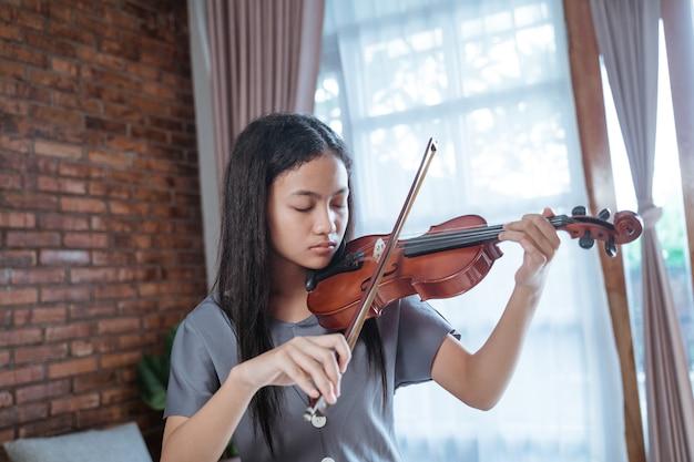 Азиатская девушка играет на скрипке в одиночестве в комнате