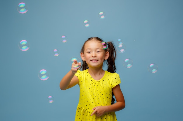 Asian girl playing with soap bubbles in the studio on a blue