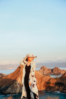 Asian girl posing on top mountain with blurry background of hills and sea at padar island