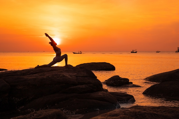 Asian girl practice yoga on the beach sunrise morning day