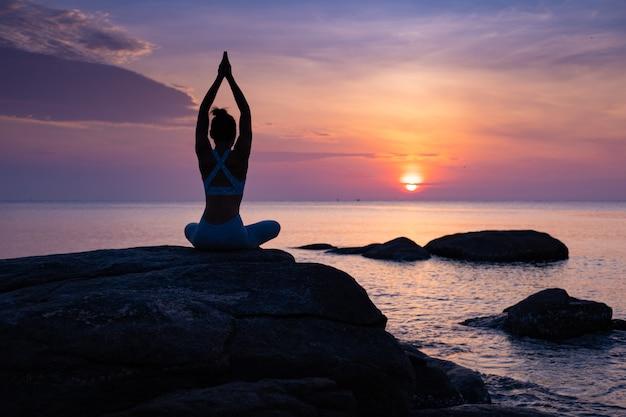Asian girl practice yoga on the beach sunrise morning day