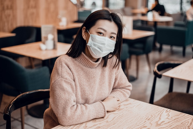 Asian girl in a protective mask is sitting in a school or cafe. a beautiful woman in a medical mask so as not to get the virus. disease prevention