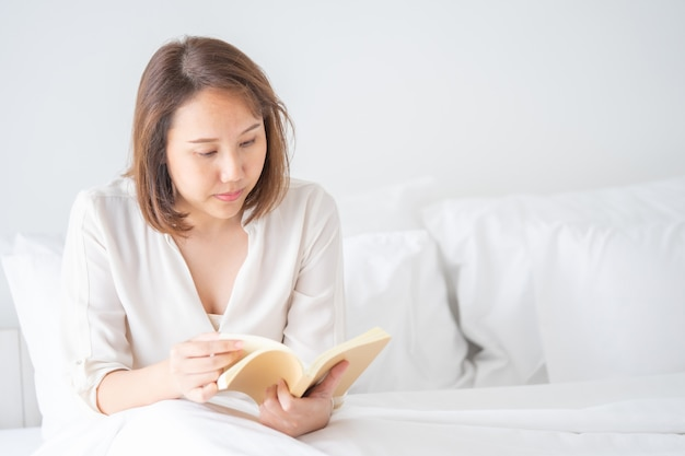 Asian girl read books after waking up in the morning. it makes you feel bright