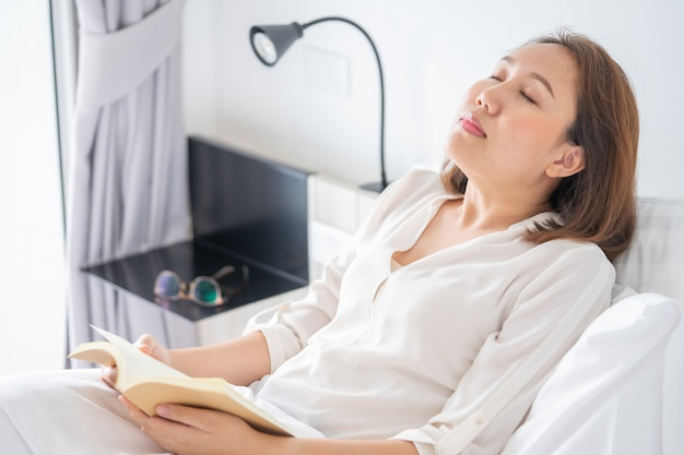 Asian girl read books while sleeping. man book cover drowsiness causes sleep.