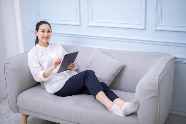 전자책을 읽고 집에서 디지털 태블릿으로 일하는 아시아 소녀
