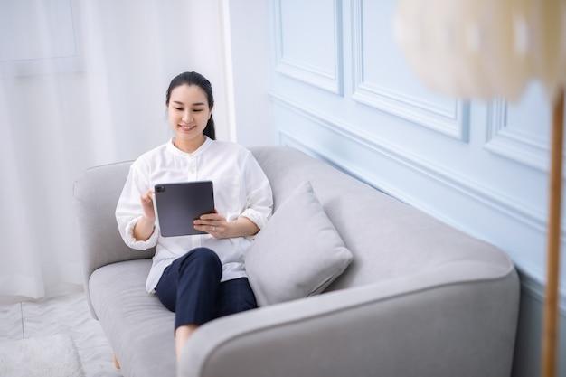 전자책을 읽고 집에서 디지털 태블릿으로 집에서 일하는 아시아 소녀