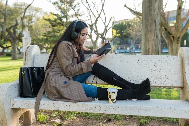 Азиатская девушка читает на скамейке в парке, слушая музыку в наушниках