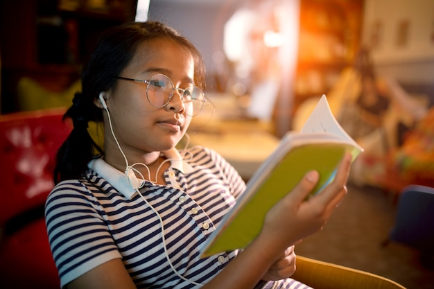 Asian girl reading school book in home liviing room