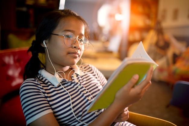 ホームリビングルームで学校の本を読んでアジアの女の子