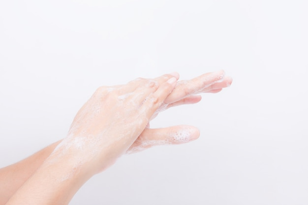Asian girl's hands are washing with soap bubbles. white background