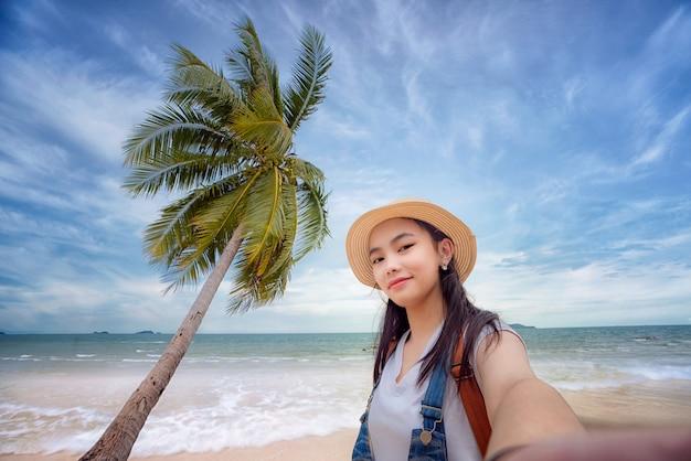 Селф азиатской девушки цифровым фотоаппаратом с пляжем и кокосом