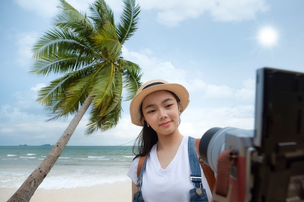 Asian girl selfie by digital camera with beach and coconut